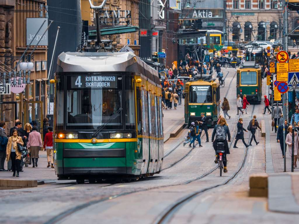 street in Helsinki with trams, bikes, and people.