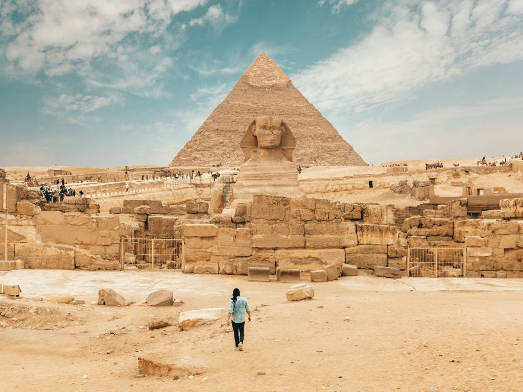 person standing in front of the pyramids in Egypt