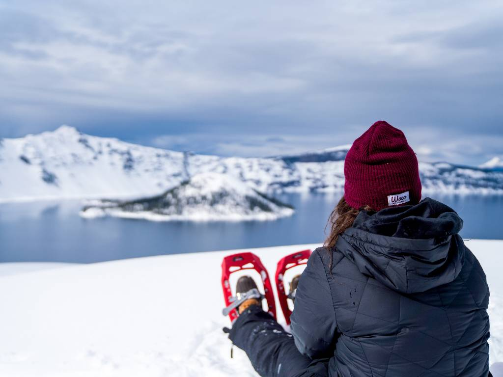 woman snowshoeing above crater lake.