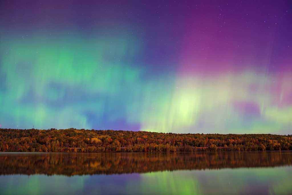colorful northern lights over lake.