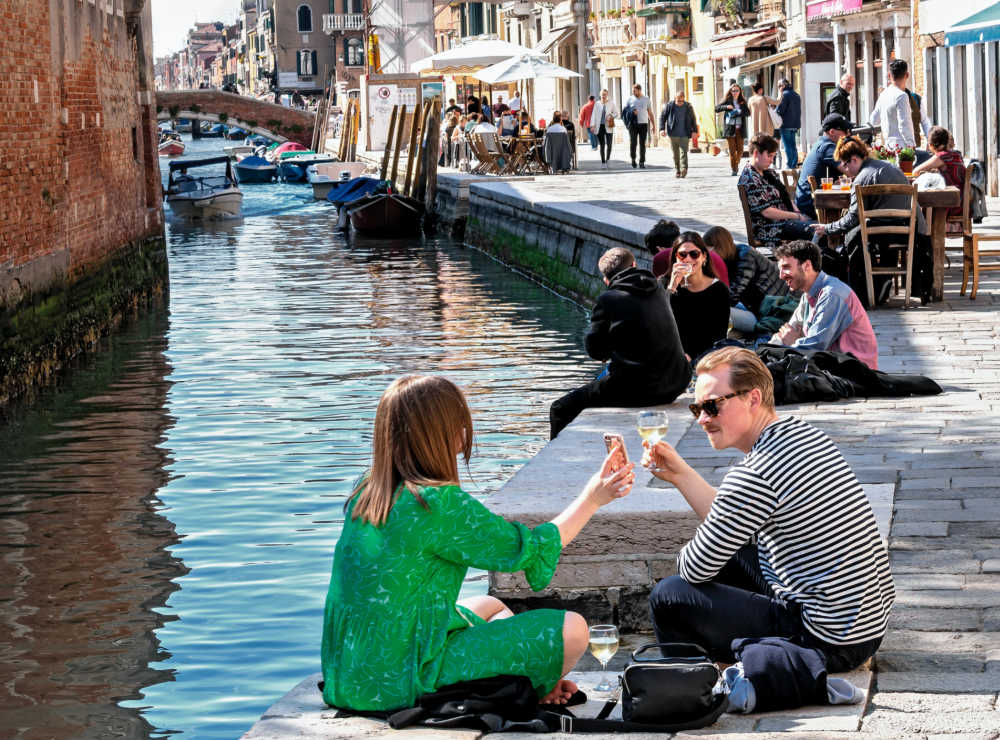 people eating and drinking along  canal in Venice.