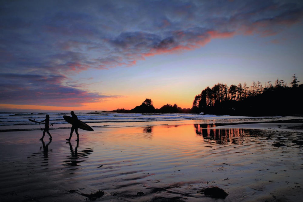 surfers on beach on Vancouver Island.