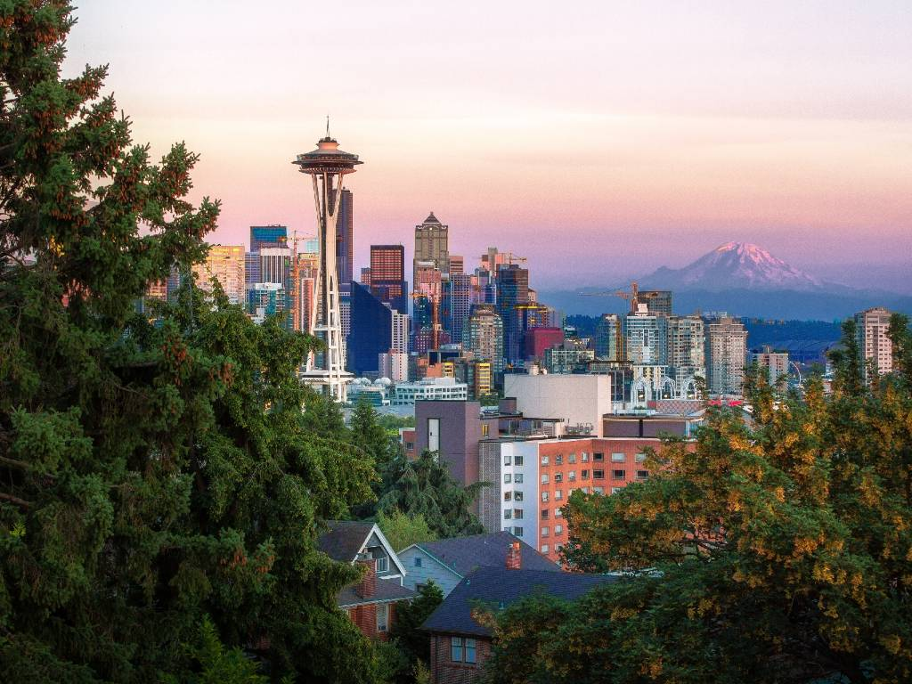 Seattle skyline with Space Needle and mountains.