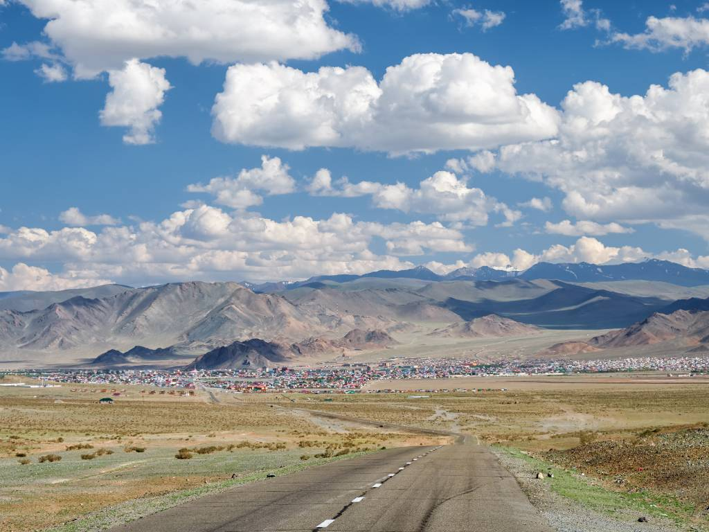 road leading to a small settlement against the mountains in Mongolia.