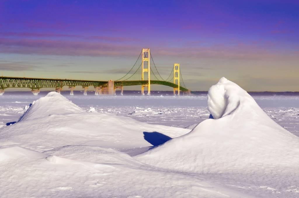snowdrift with a backdrop of the Mackinac Bridge.