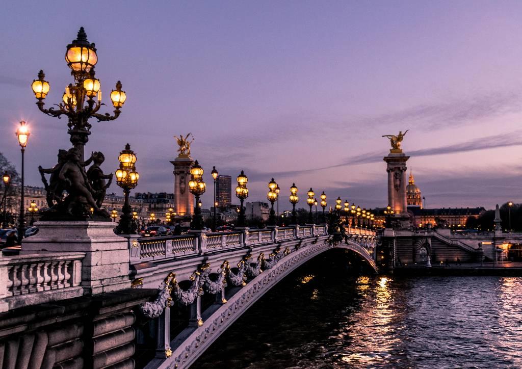 Paris bridge lit at night.