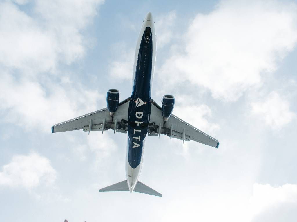 looking up at Delta plane flying overhead.