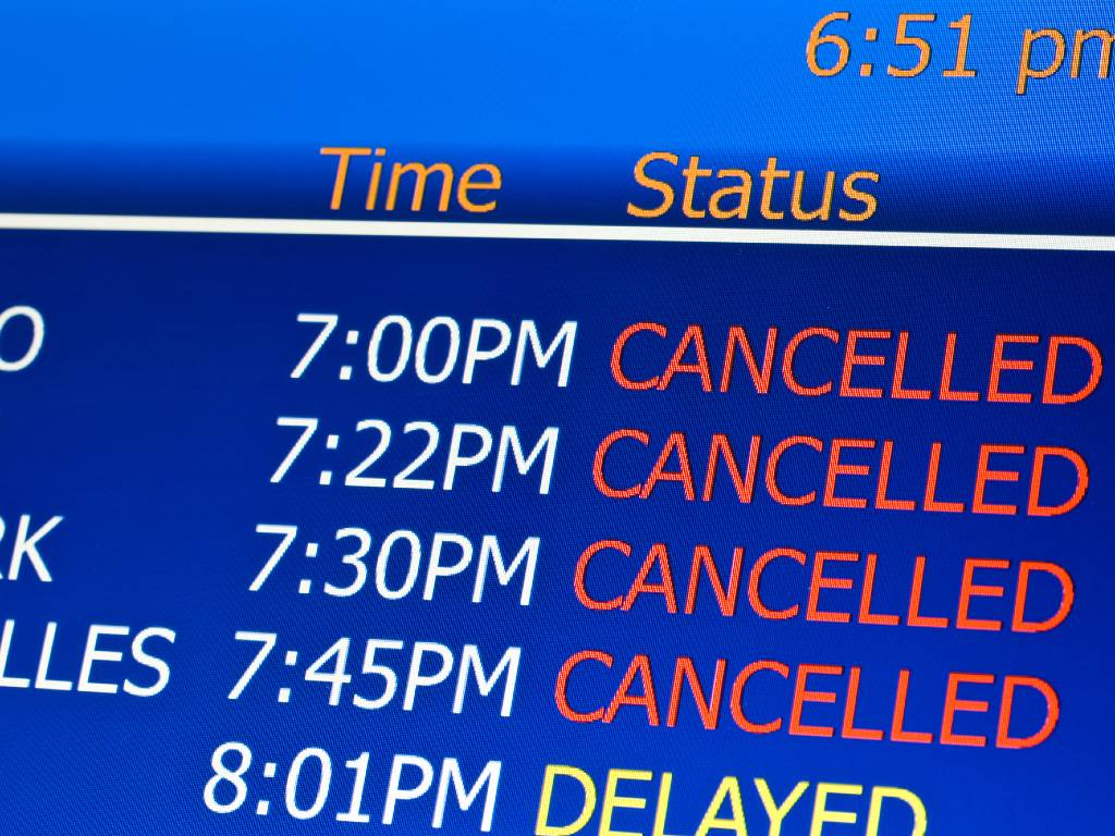 airport screen with list of canceled flights.