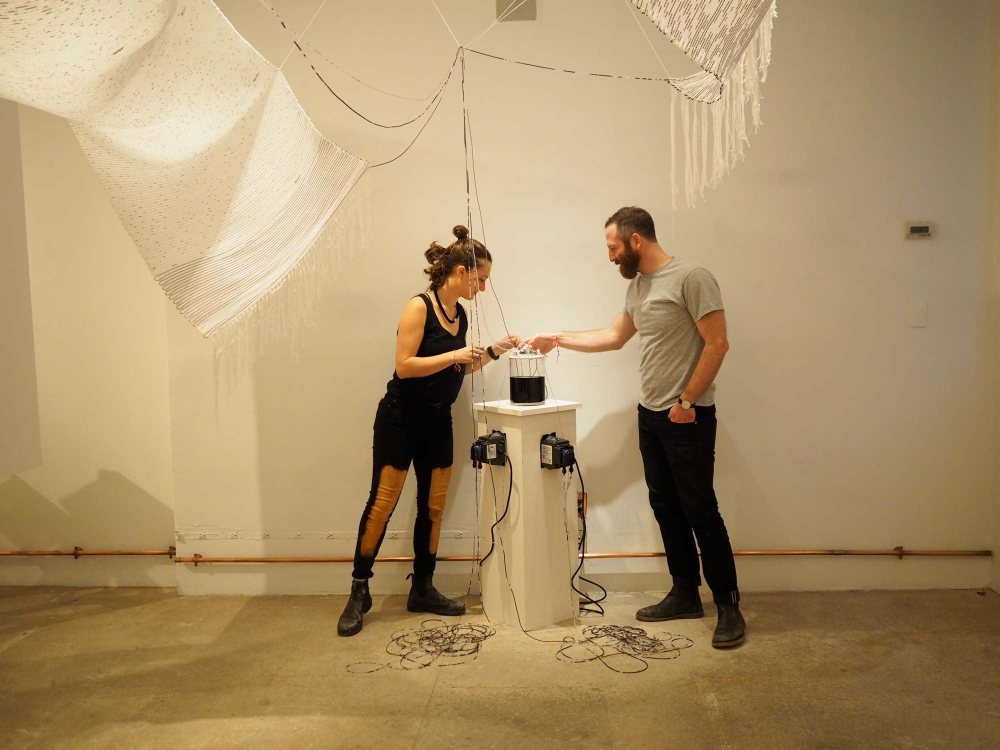 Two collaborators of Soft Monitor standing over a device that is connected to a digital textile.