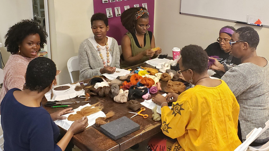 Students learning needlepoint felting around a table.