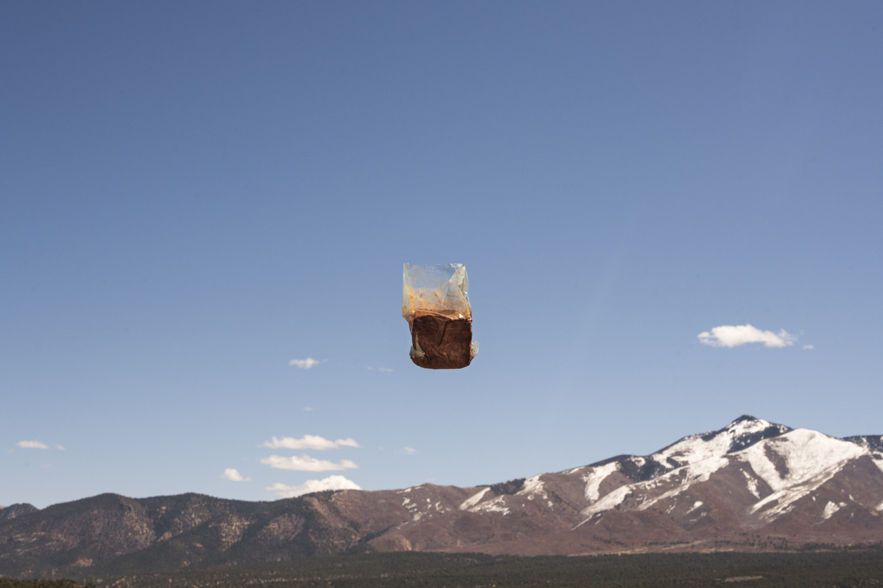 Bag of red clay suspended mid-frame in the air against a blue sky over snow-capped mountains.