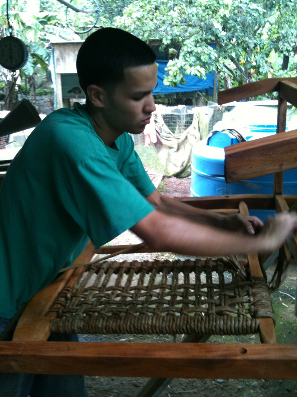 Furniture being woven by a young man in a green shirt.