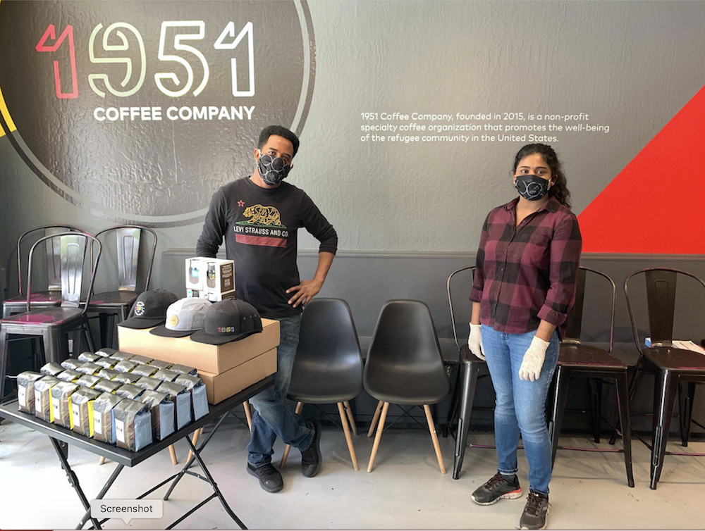Two employees of 1951 Coffee Company standing at booth with 1951 logo in background and coffee and hats for sale on table.