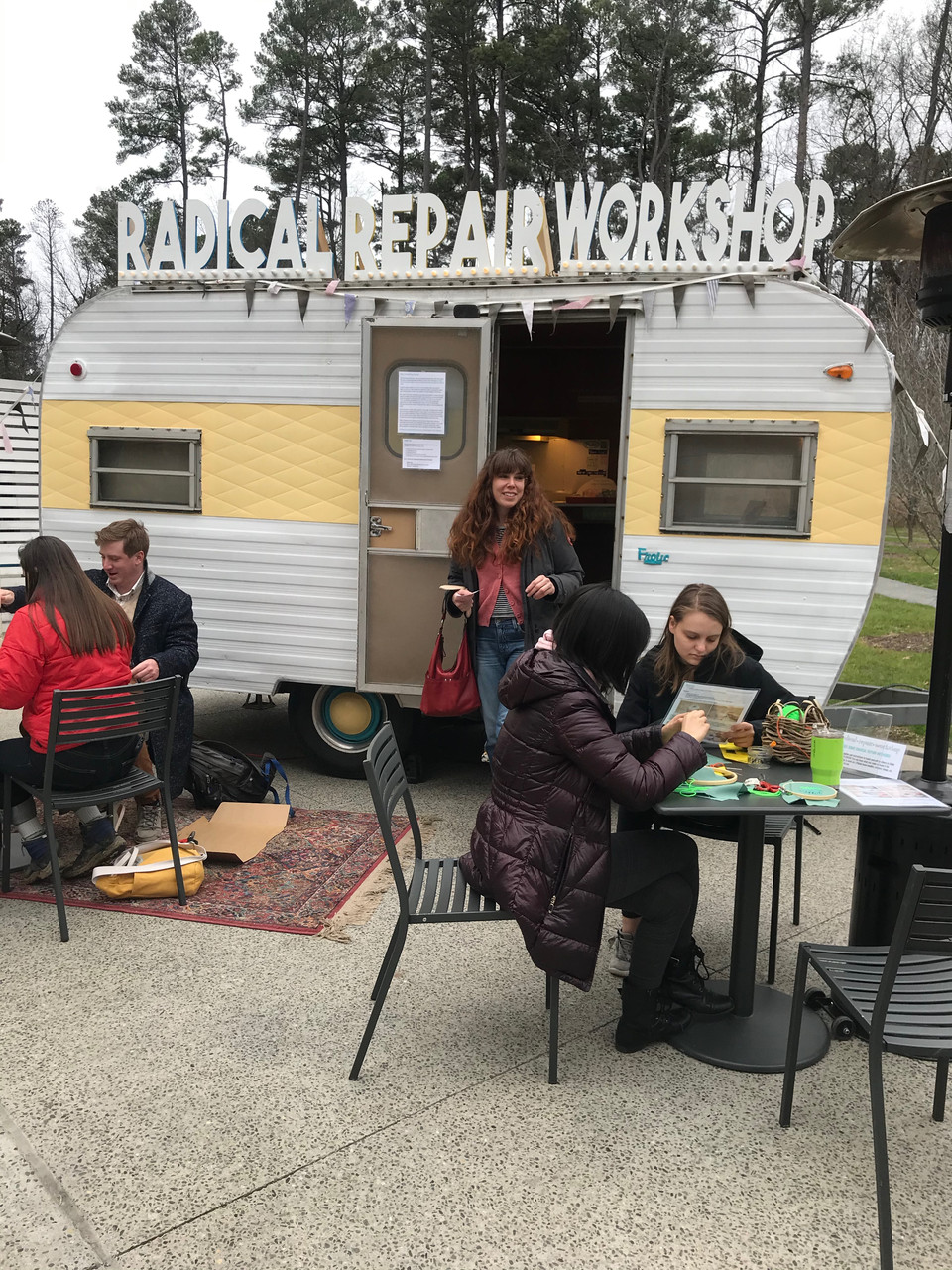 """A camper van that has the sign """"Radical Repair Workshop"""" on top of it and people at tables outside working on projects."""