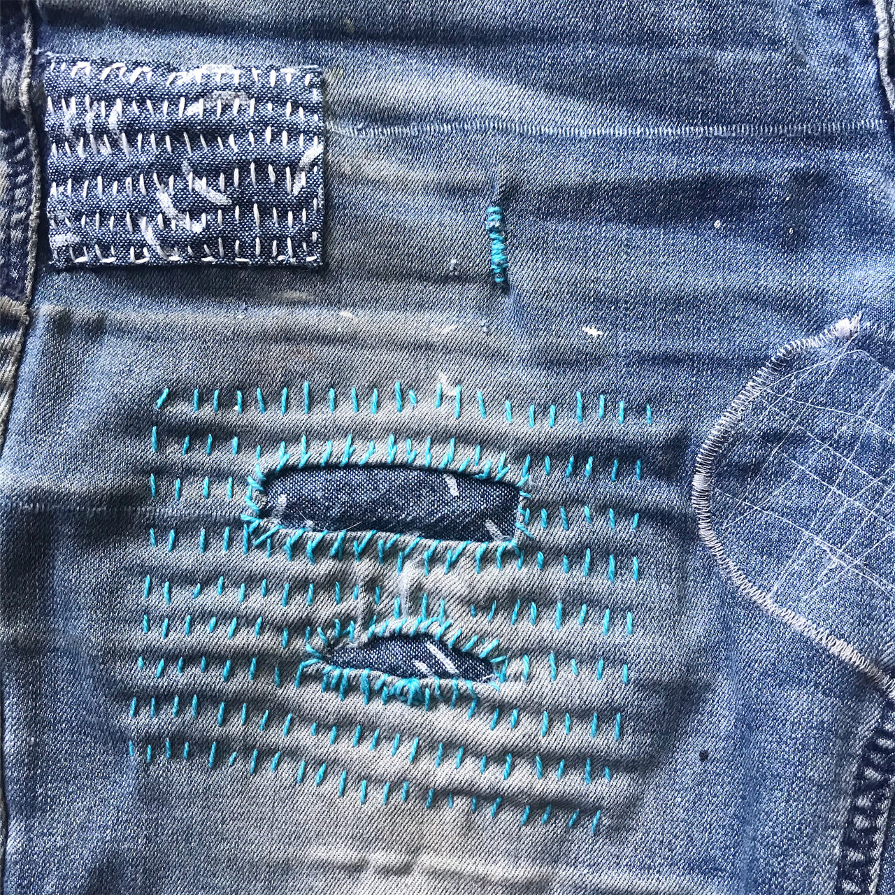 Close-up detail image of a pair of artfully mended jeans.