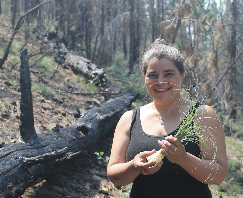 Carolyn Smith holding beargrass and smiling in foreground with wildfire-effected wilderness in background.