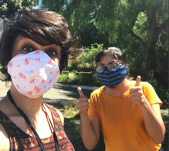 A selfie of two people wearing hand made masks, one taking the photo, and the other with two thumbs up.