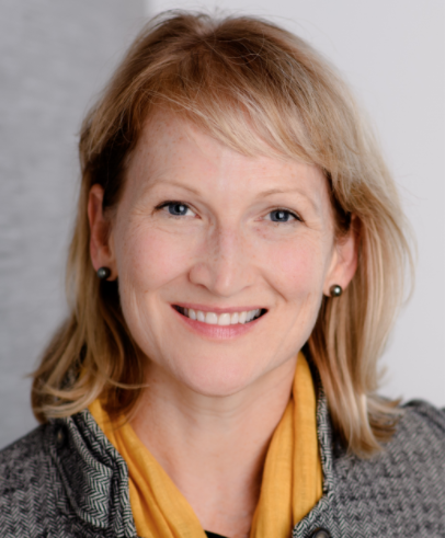 Professional headshot of smiling white woman, with a yellow scarf and a grey backdrop.