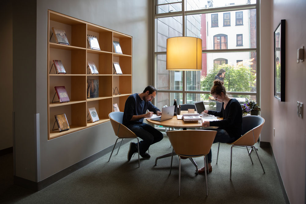 two people sitting at a table in front of a large window reading books for craft research grant
