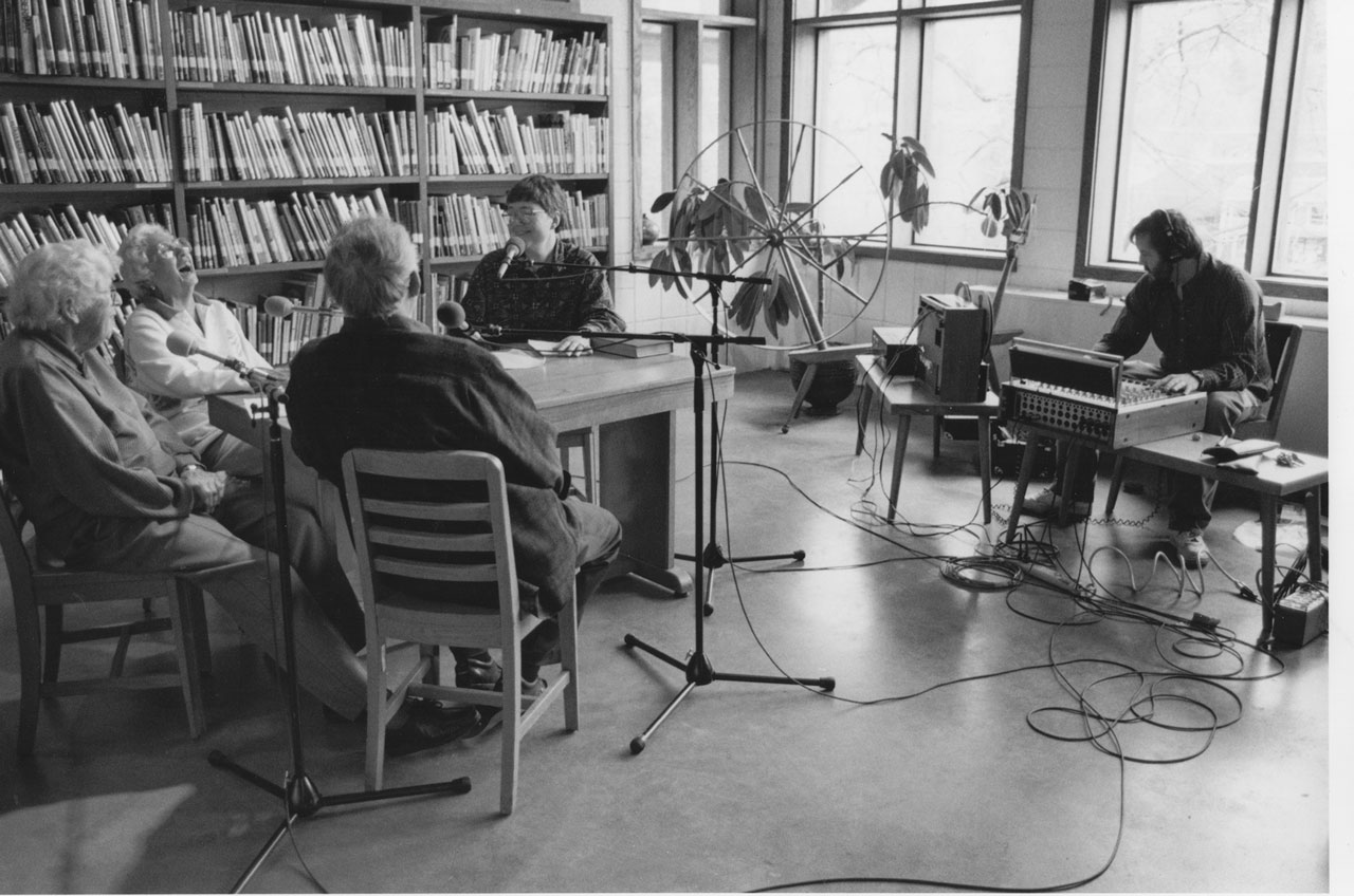 A live interview for Crafted Roots with people sitting in chairs facing a speaker sitting at a table with a microphone. Black and white image. People are smiling.