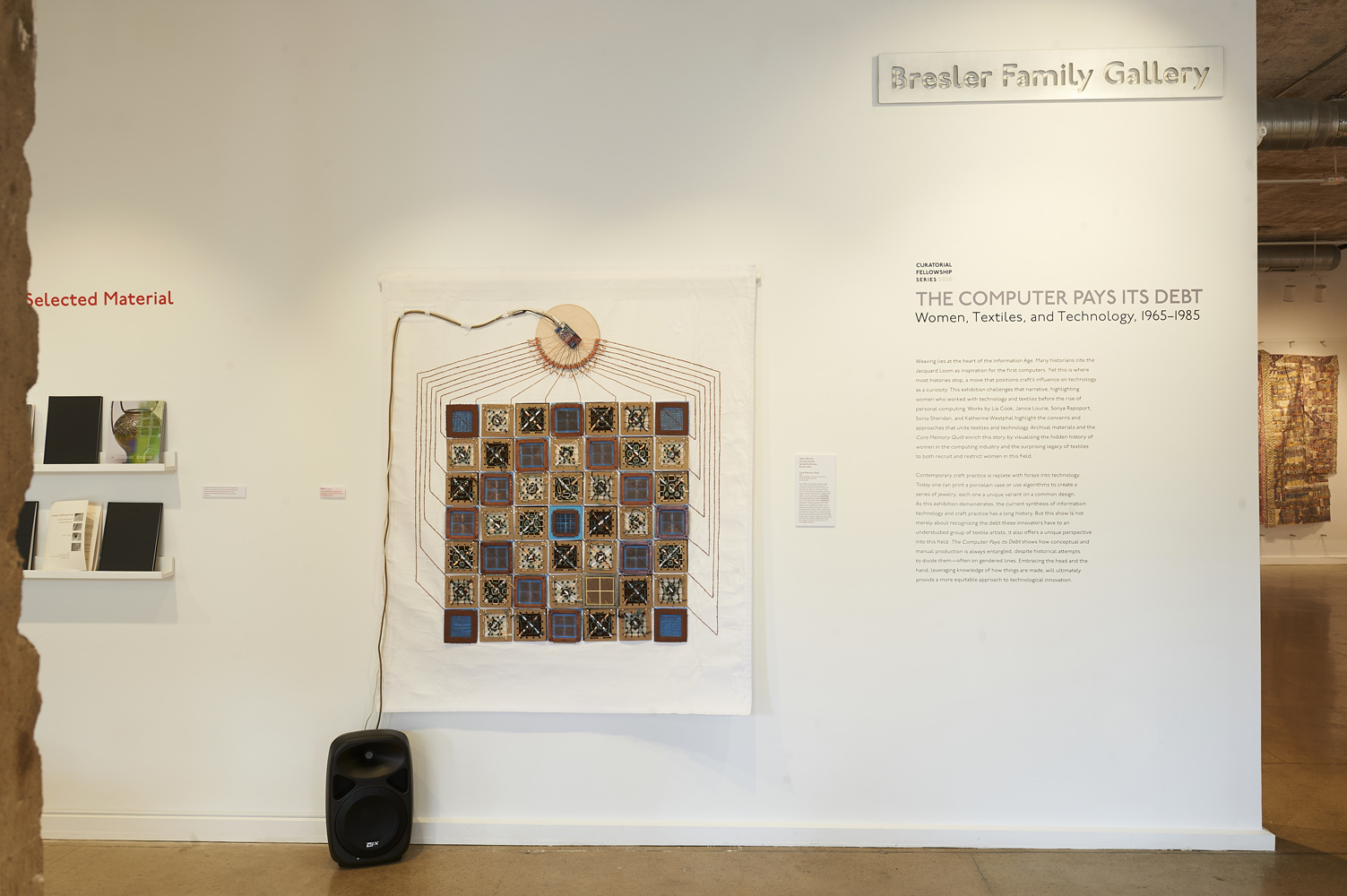 "hanging quilt in a gallery with exhibition title decal on wall next to the quilt with exhibition statement, for ""The Computer Pays Its Debt"""