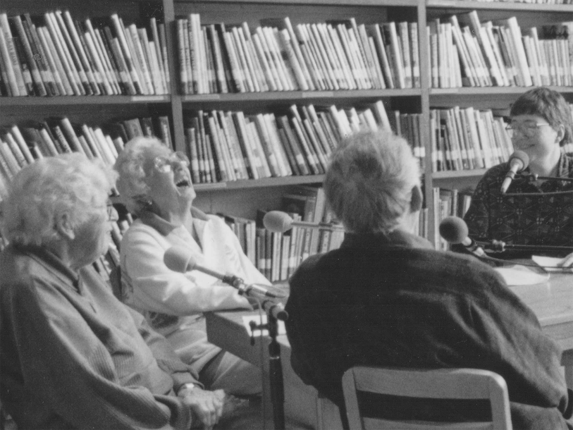 a black and white photo of four people sitting around a table with bookcases behind them, in conversation.
