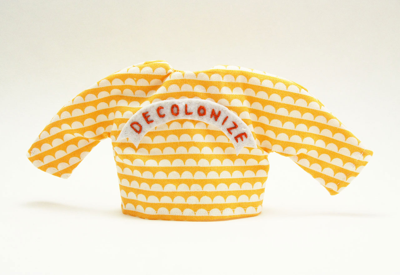 "Tiny yellow and white sweater with word ""Decolonize"" embroidered on it."