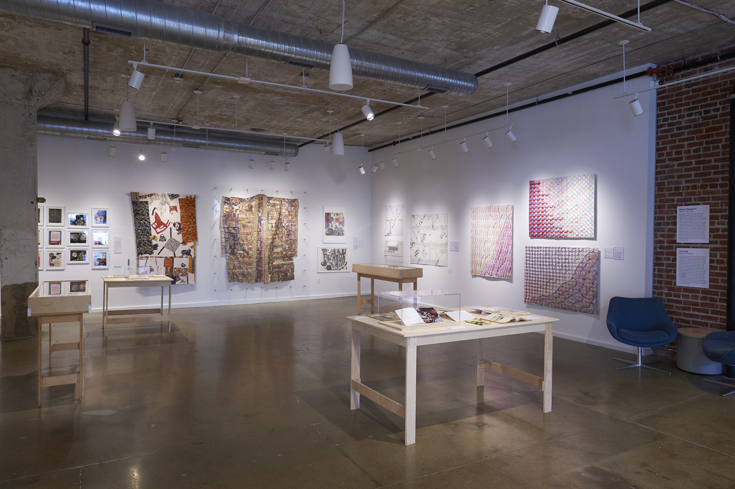 "gallery exhibition for ""The Computer Pays Its Debt"" in the Center for Craft Bresler Family Gallery, showing an assortment of textiles, clothing, quilts, and publications"