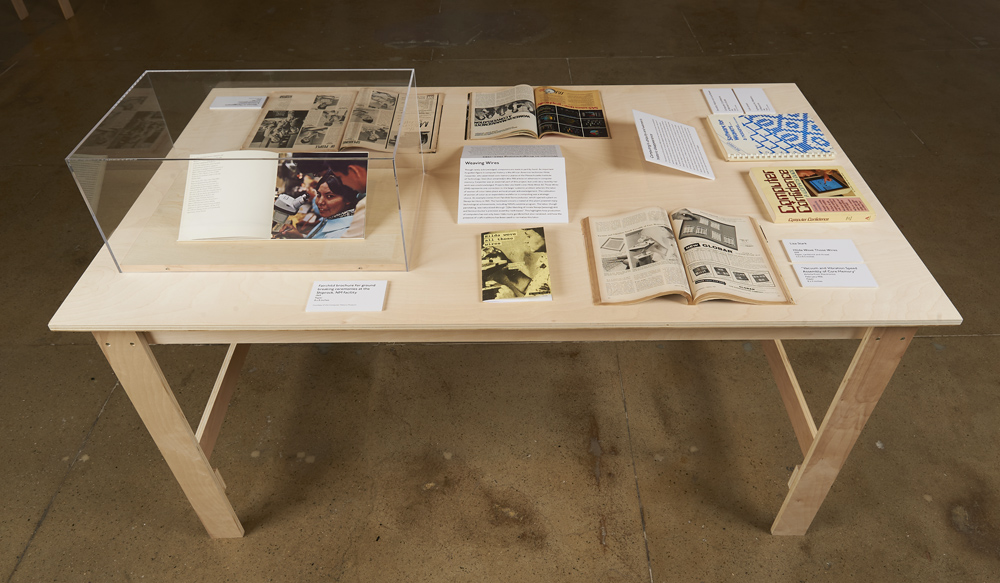 "Birchwood table in Bresler Family Gallery displaying an array of publications and artifacts for ""The Computer Pays Its Debt"""