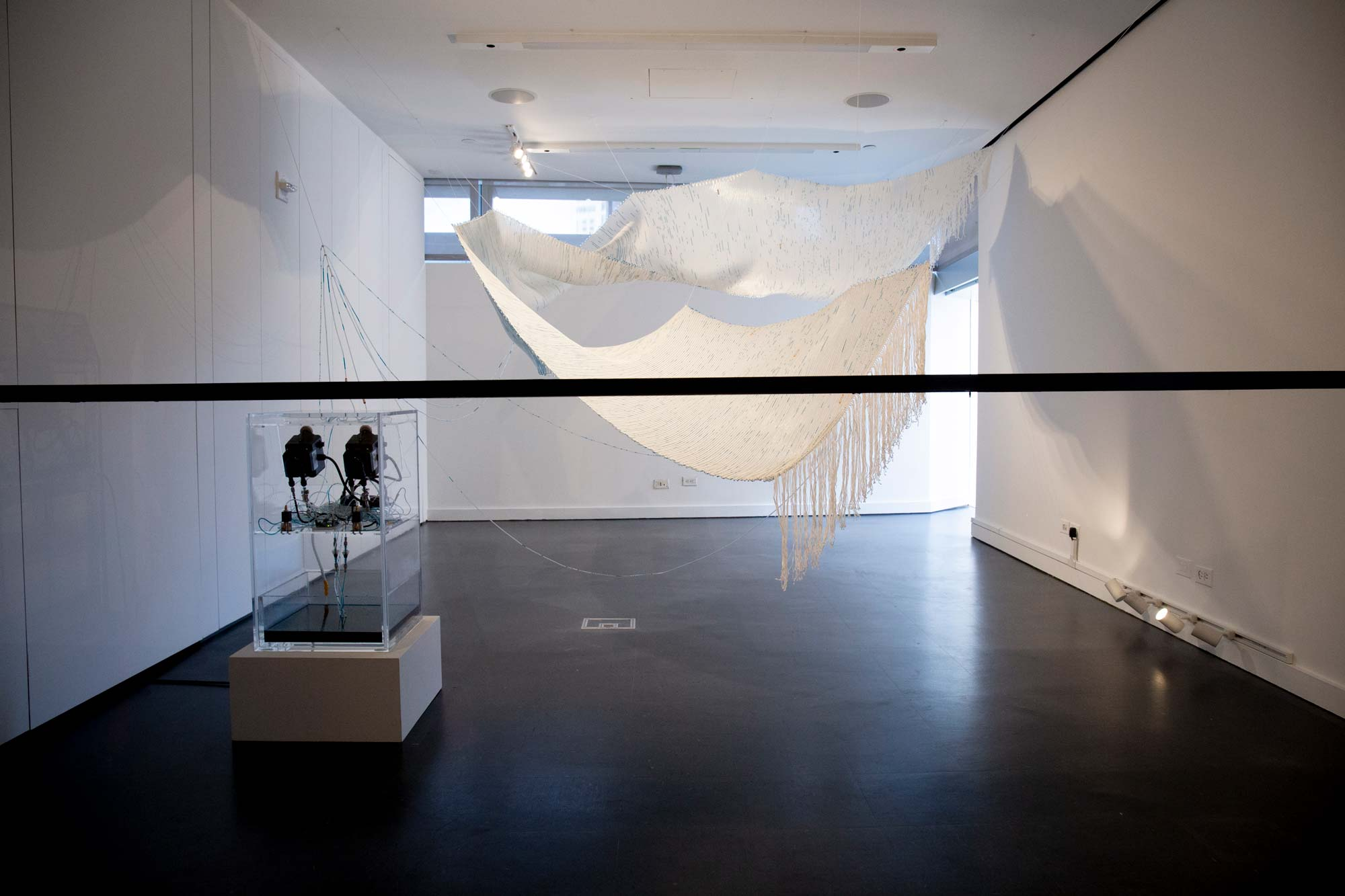 A large room with a hanging textile connected to a device that looks like a camera or projector.