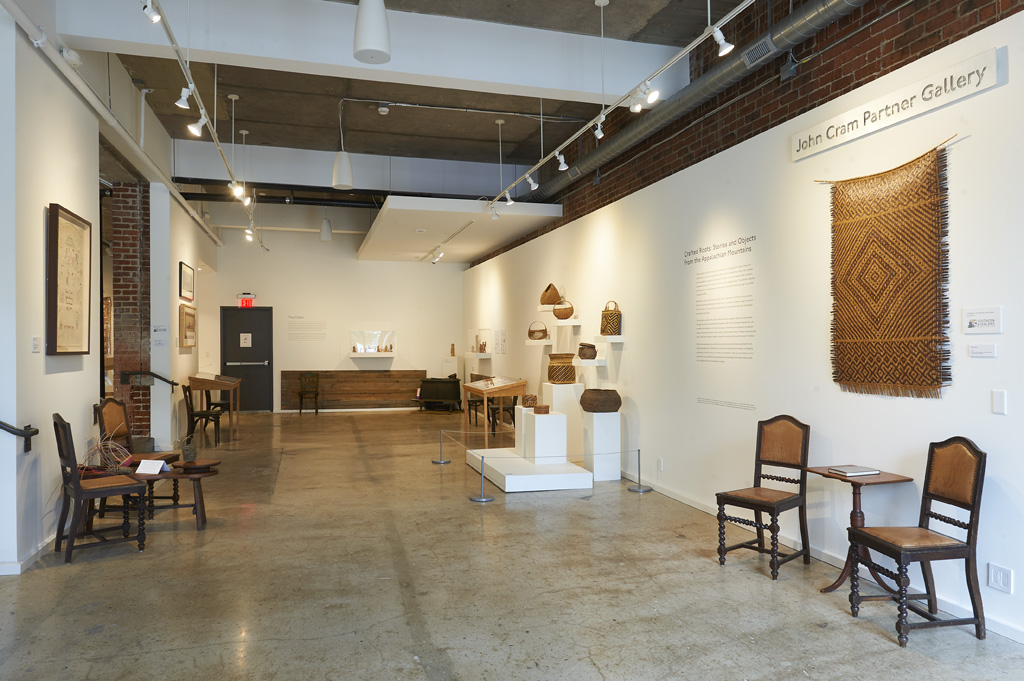 "Image of the Center's John Cram Partner Gallery with artwork from ""Crafted Roots"" exhibition, curated by Michael Hatch, in partnership with Warren Wilson College."