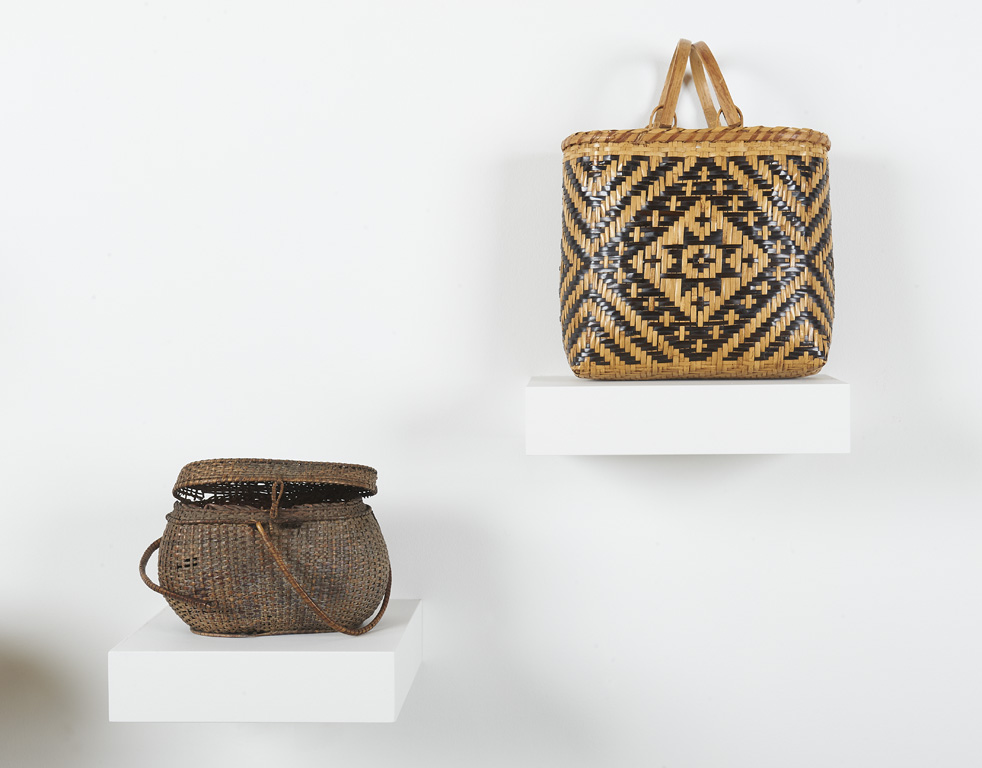 Pictured are two handwoven baskets. Basket to left is dark brown and round, with a lid. Basket on the right two-toned, patterned, and handled.