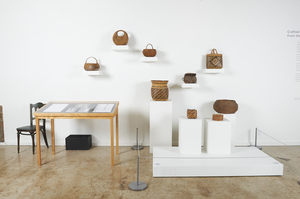 Pictured are nine handwoven baskets on pedestals. To the left of baskets is a glass-top vitrine case with printed material related to the baskets.