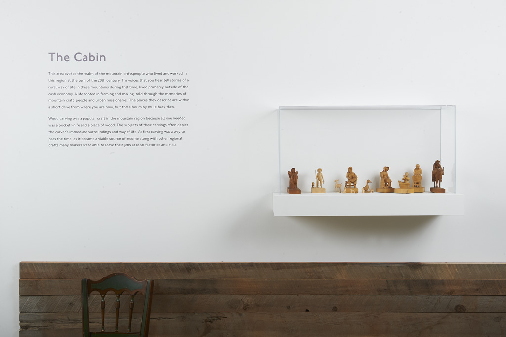 Enclosed vitrine with thirteen hand carved wooden figurines.