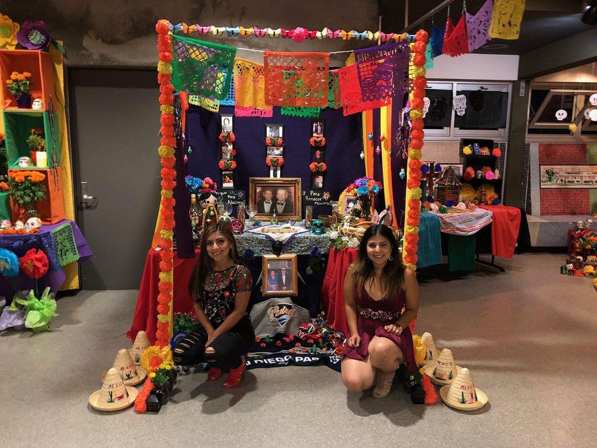 two woman crouching in front of a dia de los muertos altar, smiling at the camera. the altar is heavily decorated in colorful items and is indoors