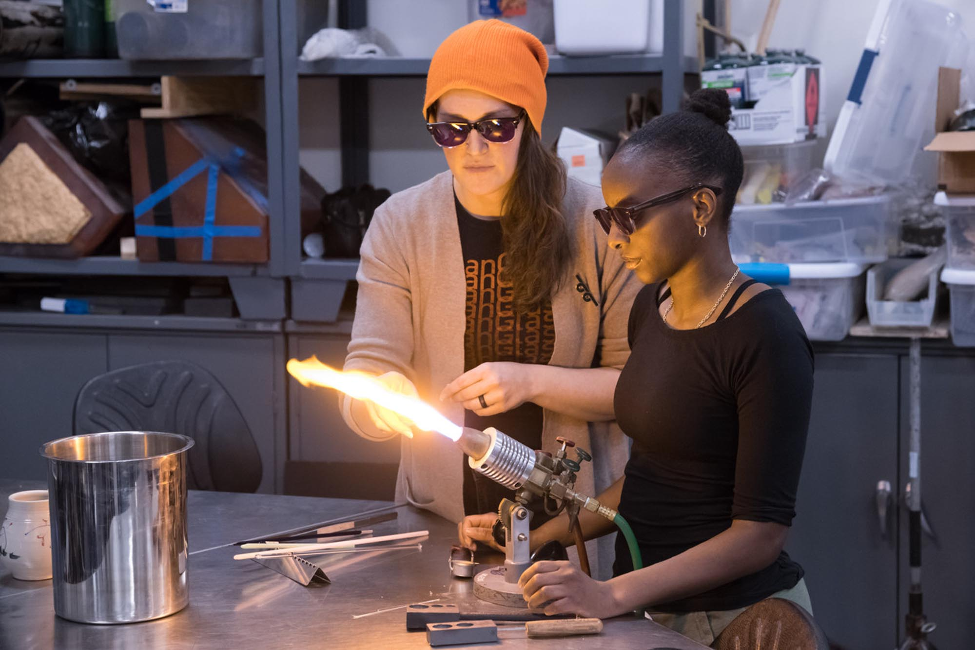 two people working on glass with a torch, wearing goggles
