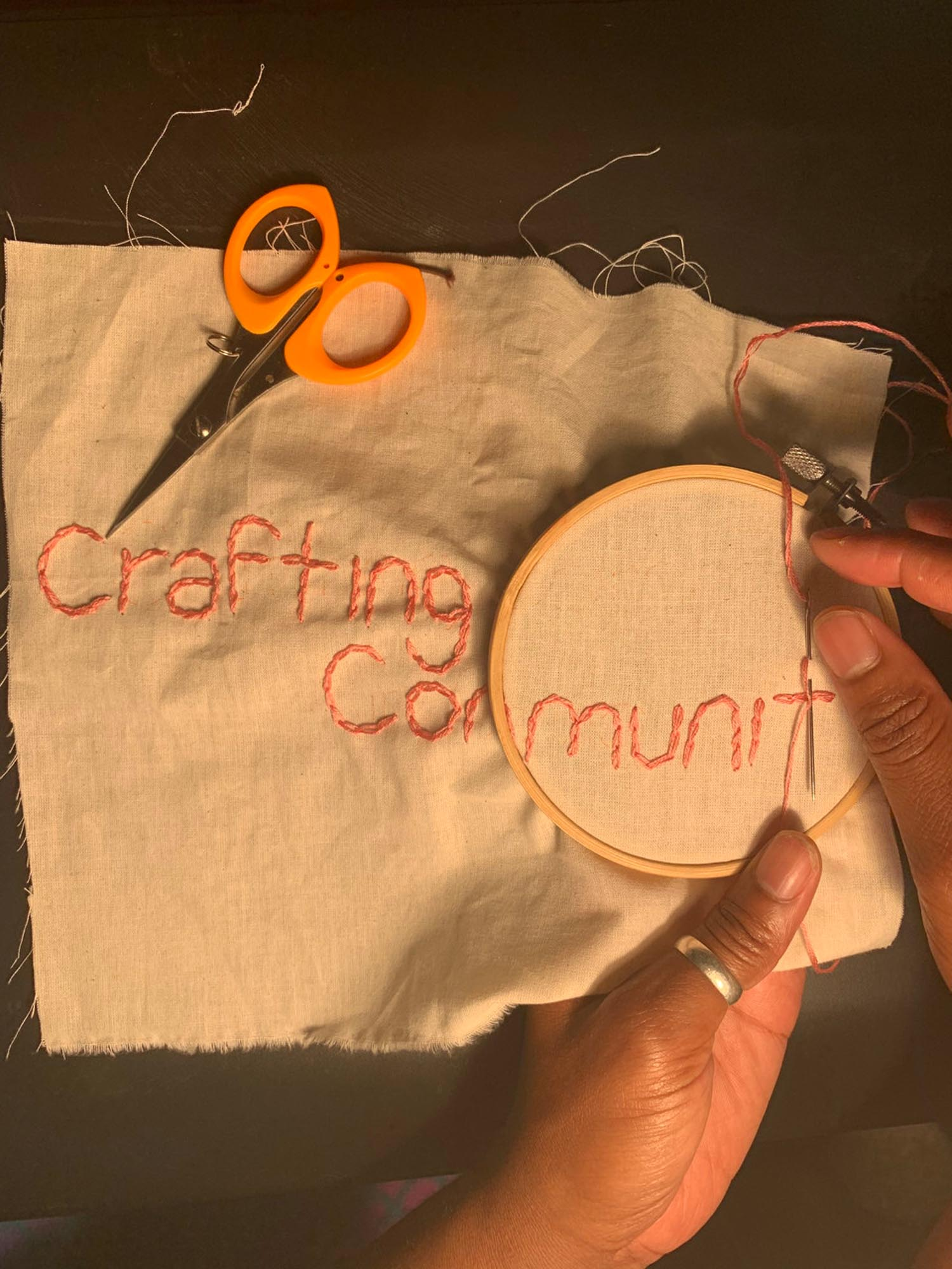 Brown Hand chain stitch the words Crafting Community into a plain muslin fabric with pink thread. Orange handled scissors lie on the table nearby.
