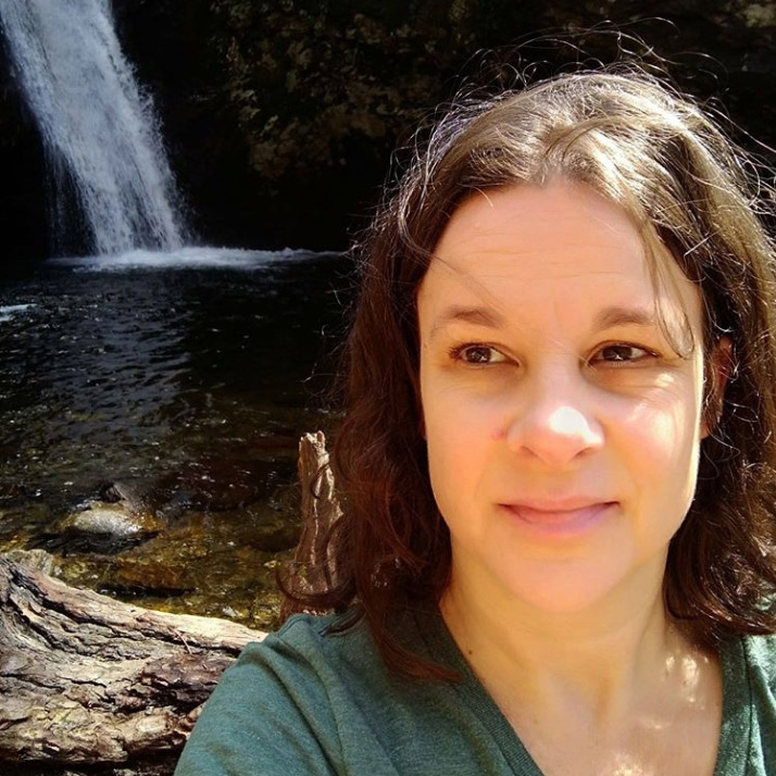 a selfie of a woman with curly brown hair standing outside by a waterfall