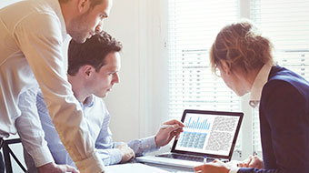 Business advisers looking at normalisation adjustment on a computer