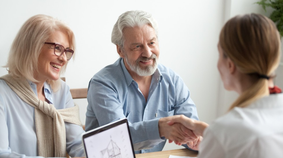 older couple shaking hands with their business advisor