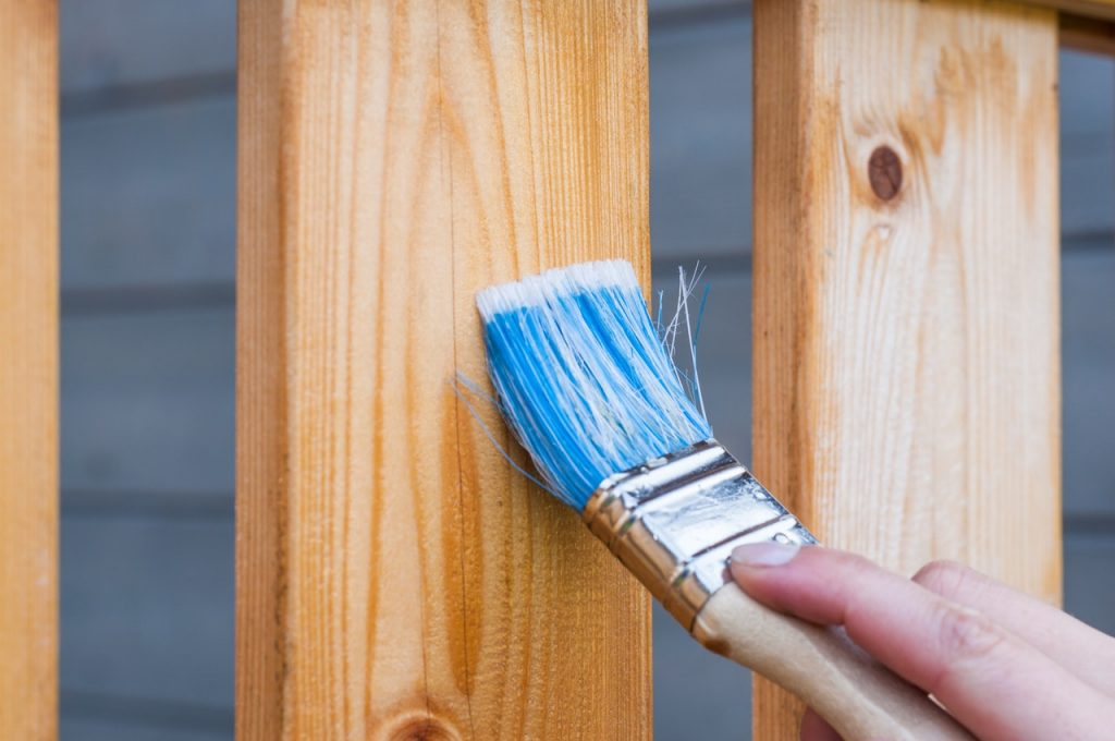 photo of a hand holding a paintbrush and painting a fence