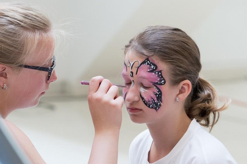 Uma mão pintando com um pincel uma borboleta roda no rosto da filha - Figura 1. Ao pintar o rosto da criança evite pintar os olhos. (Fonte: Pixabay)