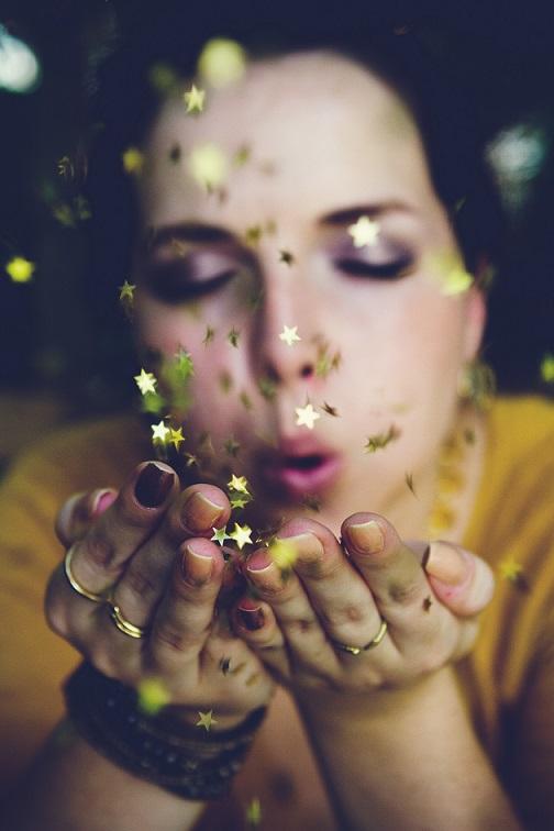 Mulher sobrando glitters de estrelas douradas - Figura 2. Queridinhos do carnaval, os glitters podem causar pesões nos olhos. (Fonte: Pixabay)