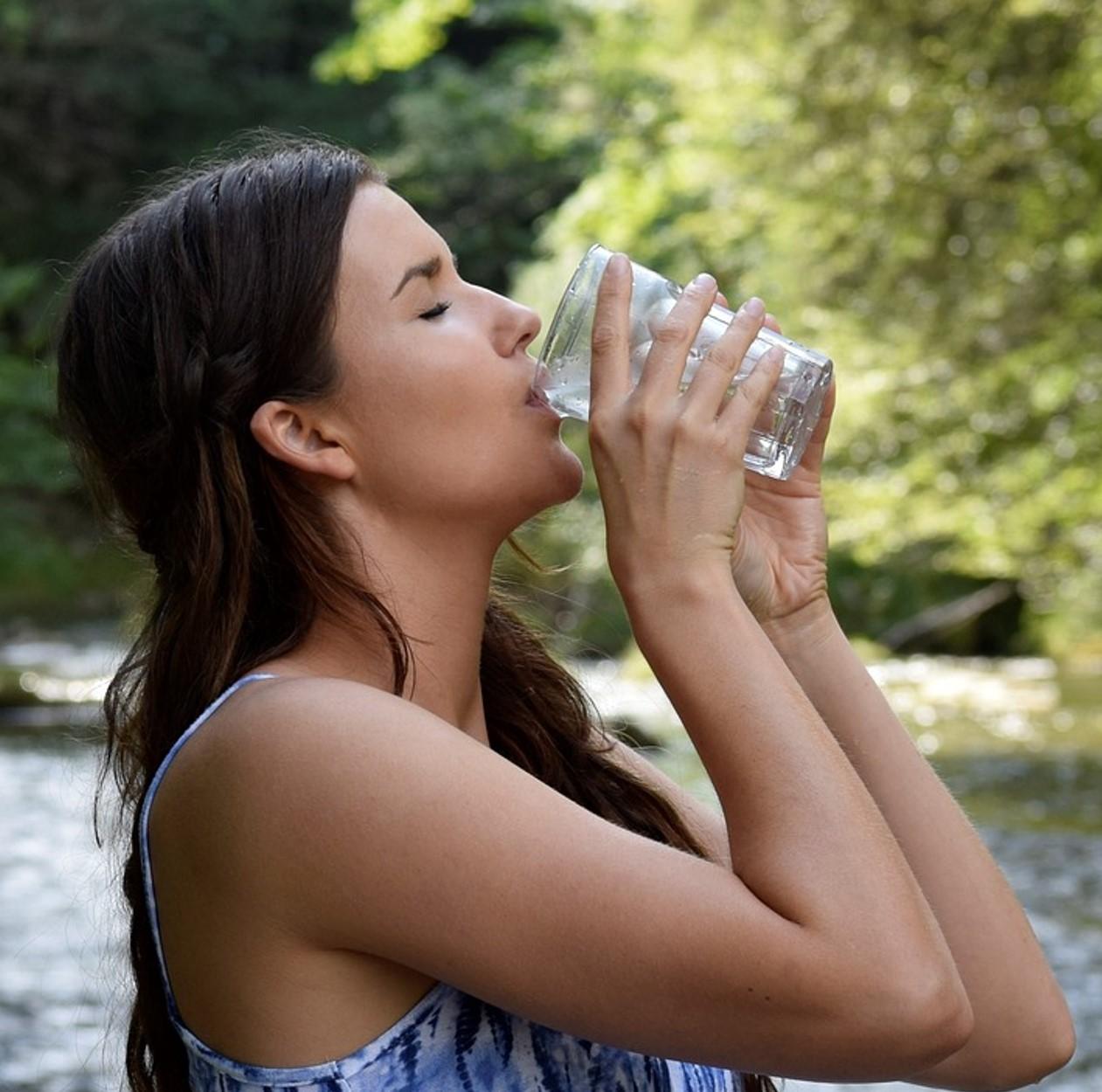Uma mulher morena, bebendo água em um copo de vidro - Beba bastante água, mantenha o seu corpo hidratado. (Fonte: Pixabay)