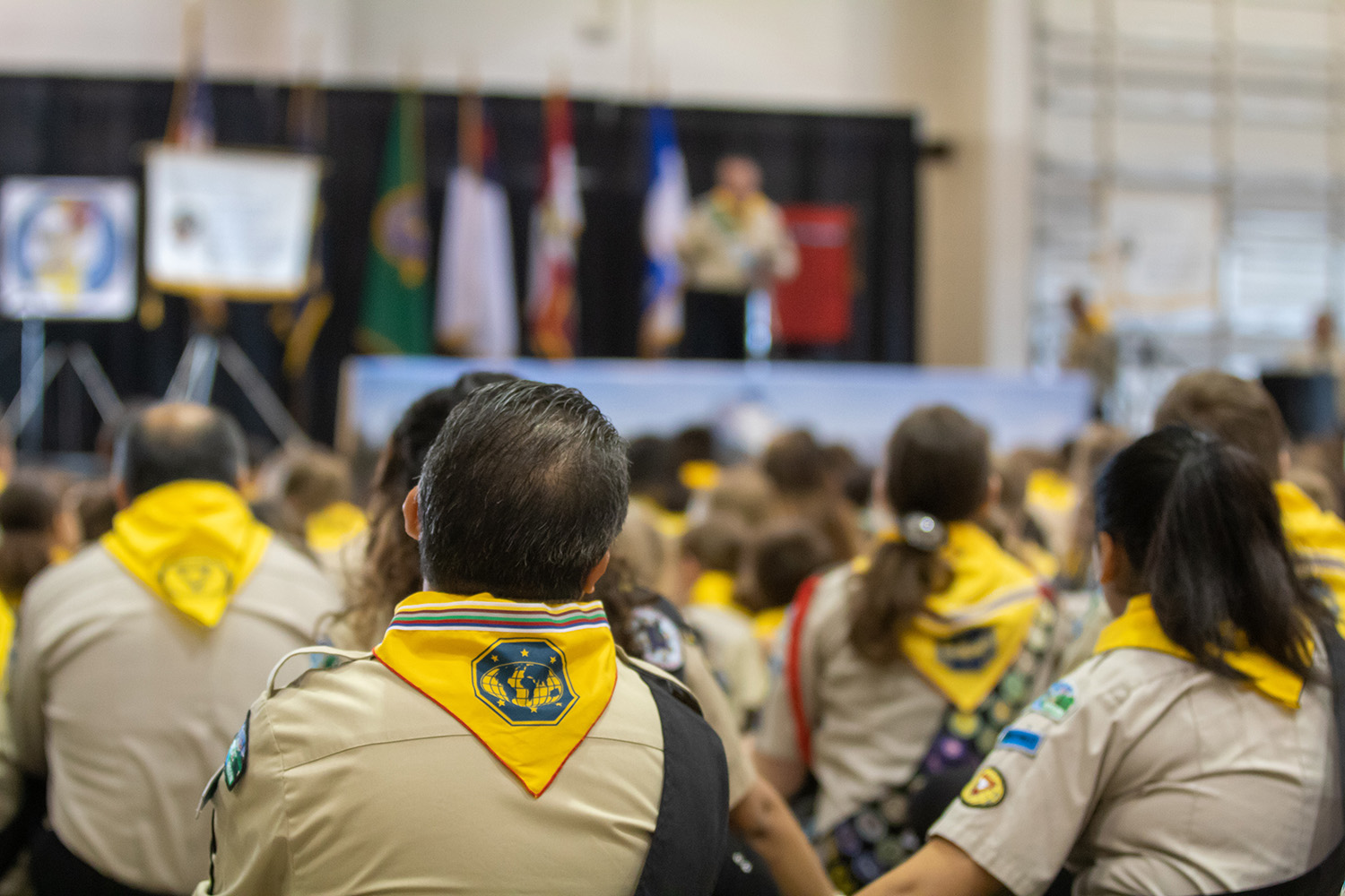 Pathfinders in uniforms setting on floor listing to person on stage