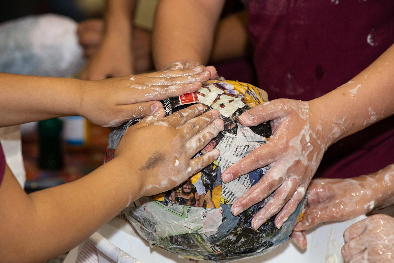 Hands making paper mache ball