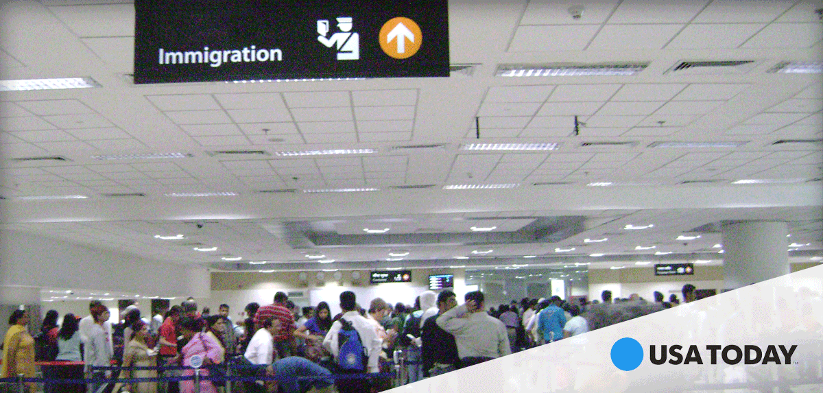 Image of an immigration center where people are waiting in a queue