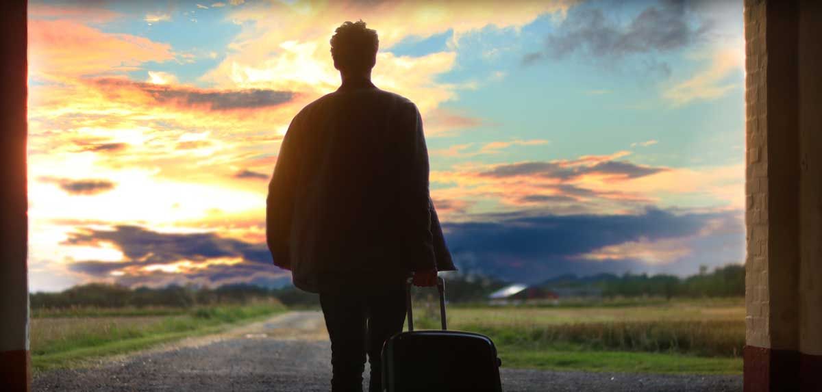 Man pulls rolling luggage, walks toward sunrise in quest of a fulfilling tech career