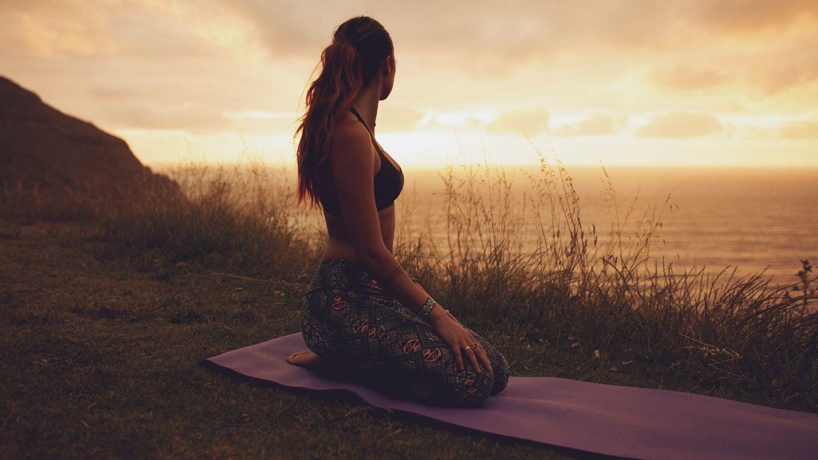 Woman on a yoga mat outdoors during sunset to improve work-life balance and mental wellness.