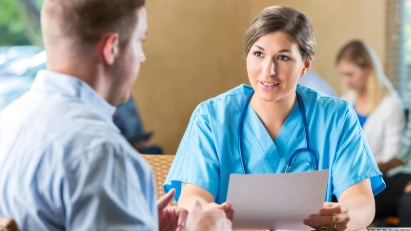 Travel nurse interviewing man in a blue dress shirt.